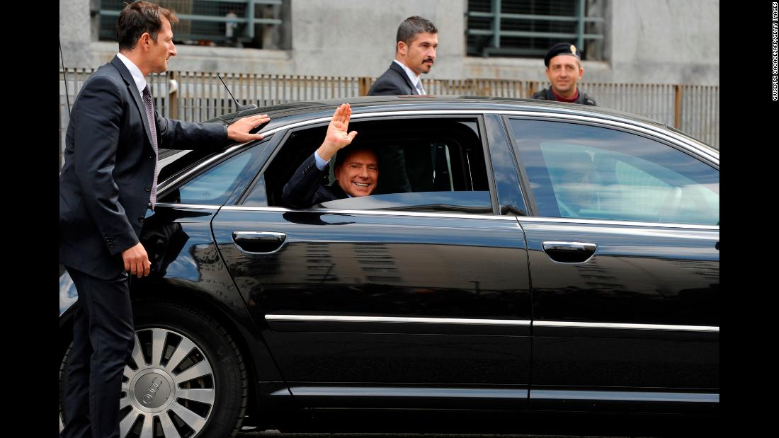 Berlusconi waves as he leaves a court in Milan in September 2011.