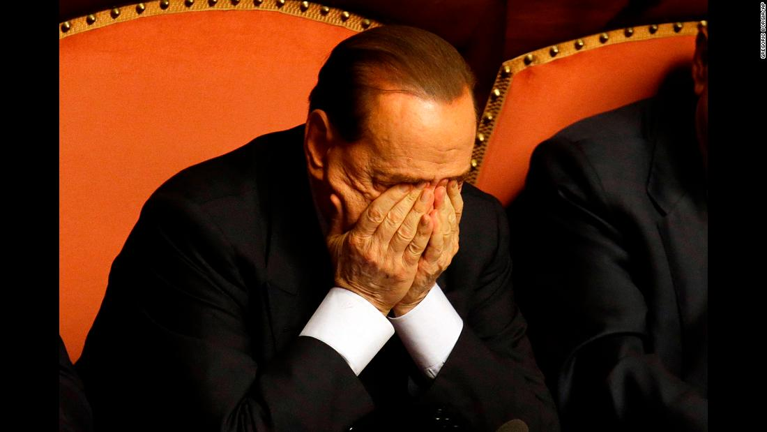 Berlusconi rubs his eyes after delivering a speech in Rome in October 2013. That month, Berlusconi was preliminarily indicted on allegations he bribed a senator to support his party in 2006. He would be convicted in 2015 and banned from holding public office for five years.