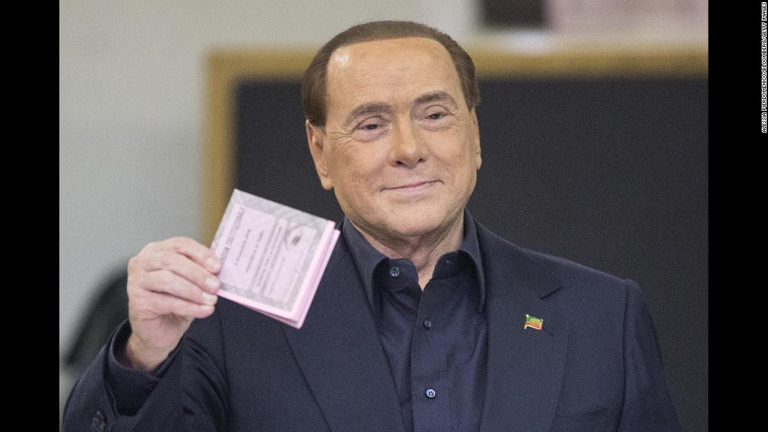 Berlusconi holds his ballot before casting his vote in the referendum on constitutional reform in December 2016.