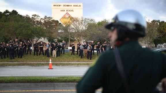 PARKLAND, FL - FEBRUARY 28: Police officers stand in front of Marjory Stoneman Douglas High School as student arrive to attend classes for the first time since the shooting that killed 17 people on February 14  at the school on February 28, 2018 in Parkland, Florida.  Police arrested 19-year-old former student Nikolas Cruz for the 17 murders.  (Photo by Joe Raedle/Getty Images)
