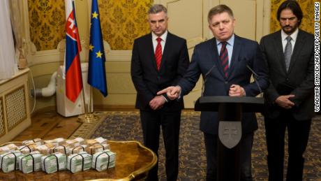 Slovak Prime Minister Robert Fico, center, points to the cash reward in a news briefing Tuesday.