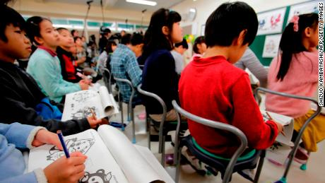 Elementary school students look at mascot choices for the Tokyo 2020 Olympics in Chofu, Tokyo.