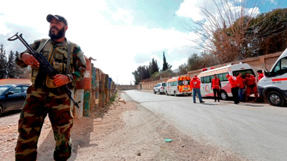 A Syrian troop stands guard near ambulances waiting to transport injured people at the Wafideen checkpoint on the outskirts of Damascus on Wednesday.