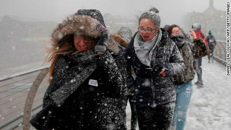 Pedestrians cross the Millennium Bridge as heavy snowfall hits London.