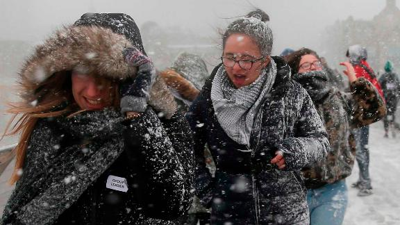 Pedestrians cross the Millennium Bridge as heavy snowfall hits London.