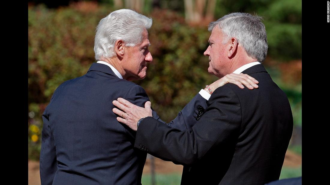 Former President Bill Clinton, left, greets Franklin Graham as he arrives to pay his respects on February 27.
