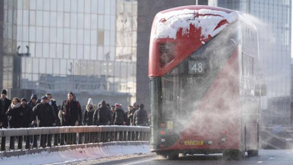 Snow blows off a bus as commuters cross London Bridge after snow hit London overnight.
