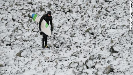 A surfer walks over snow-covered rocks after surfing in Redcar, northeast England.