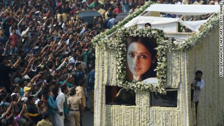 Indian fans watch as the funeral cortege of the late Bollywood actress Sridevi Kapoor passes through Mumbai on February 28, 2018. Thousands of heartbroken fans lined the streets of Mumbai February 28 as India said farewell to Bollywood legend Sridevi Kapoor following her shock death from accidental drowning in a Dubai hotel bathtub aged just 54. / AFP PHOTO / PUNIT PARANJPE        (Photo credit should read PUNIT PARANJPE/AFP/Getty Images)