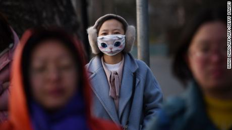 A woman wears a mask in Beijing