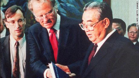 "PYONGYANG, SOUTH KOREA:  Billy Graham (C), the American evangelist, presents his book ""Peace with God"" to North Korean President Kim il-Sung (R) 02 April 1992 in Pyongyang. Graham, (son of a dairy farmer, born in 1918 in Charlotte, NC), attended Florida Bible Institute and was ordained a Southern Baptist minister in 1939 and quickly gained a reputation as a preacher. During the 1950s he conducted a series of highly organized revivalist campaigns in the USA and UK, and later in South America, the USSR and Western Europe. (Photo credit should read AFP/Getty Images)"
