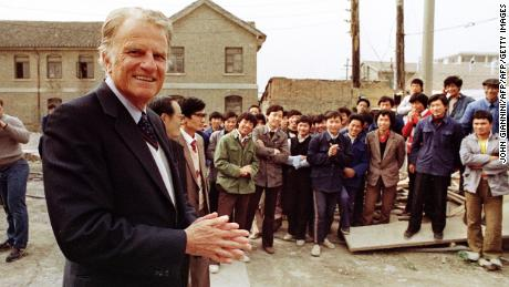 HUAIYIN, CHINA:  Billy Graham (L), the American evangelist, addresses Chinese faithful 20 April 1988 in front of his wife Ruth birthplace in Huaiyin, Jiangsu province, China. Graham, (son of a dairy farmer, born in 1918 in Charlotte, NC), attended Florida Bible Institute and was ordained a Southern Baptist minister in 1939 and quickly gained a reputation as a preacher. During the 1950s he conducted a series of highly organized revivalist campaigns in the USA and UK, and later in South America, the USSR and Western Europe. (Photo credit should read JOHN GIANNINI/AFP/Getty Images)