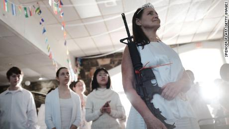 "NEWFOUNDLAND, PA - FEBRUARY 28:  A woman holds an AR-15 rifle during a ceremony at the World Peace and Unification Sanctuary in Newfoundland, Pennsylvania on February 28, 2018 in Newfoundland, Pennsylvania. The controversial church, which is led by the son of the late Rev. Sun Myung Moon, believes the AR-15 symbolizes the ""rod of iron"" in the biblical book of Revelation, and it has encouraged couples to bring the weapons to a ""commitment ceremony"" or ""Perfection Stage Book of Life Registration Blessing"". Officials in the rural area in the Pocono Mountains have reportedly told elementary school parents that their children will be relocated on Wednesday to accommodate the AR-15 ceremony. The semiautomatic rifles are similar to the weapons used in a Florida high school shooting two weeks earlier.  (Photo by Spencer Platt/Getty Images)"