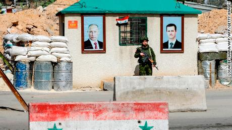 A picture taken on March 1, 2018 shows a member of the Russian military police standing guard between the portraits of Syrian President Bashar al-Assad (R) and Russian President Vladimir Putin (L) hanging outside a guard-post at the Wafideen checkpoint on the outskirts of Damascus neighbouring the rebel-held Eastern Ghouta region. / AFP PHOTO / LOUAI BESHARA        (Photo credit should read LOUAI BESHARA/AFP/Getty Images)