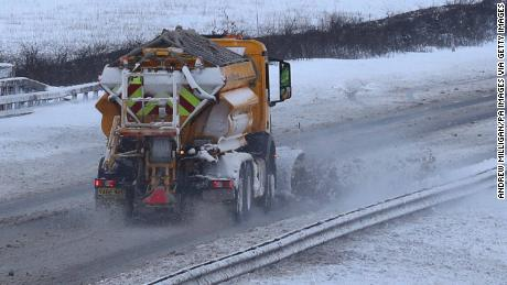 A snow plow spreads grit and clears the M9 motorway in Scotland.