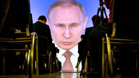 Journalists watch as Russian President Vladimir Putin gives his annual state of the nation address in Manezh in Moscow, Russia, Thursday, March 1, 2018. Putin set a slew of ambitious economic goals, vowing to boost living standards, improve health care and education and build modern infrastructure in a state-of-the-nation address. (AP Photo/Alexander Zemlianichenko)