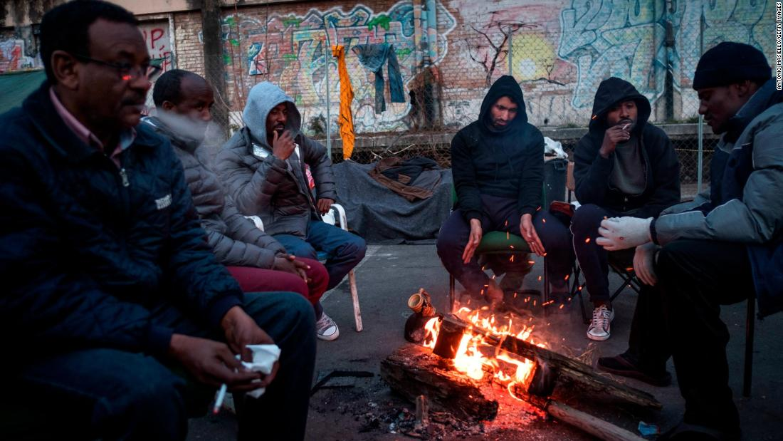 Migrants warm up around a fire at a makeshift camp in Rome in February.