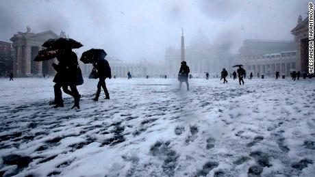 Romans trudge through the snow in St. Peter's Square on Monday.