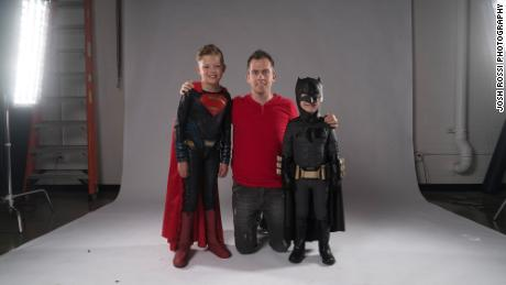 Digital artist and photographer Josh Rossi posing with nine-year-old Teagan Pettit as Superman and five-year-old Simon Fullmer as Batman.