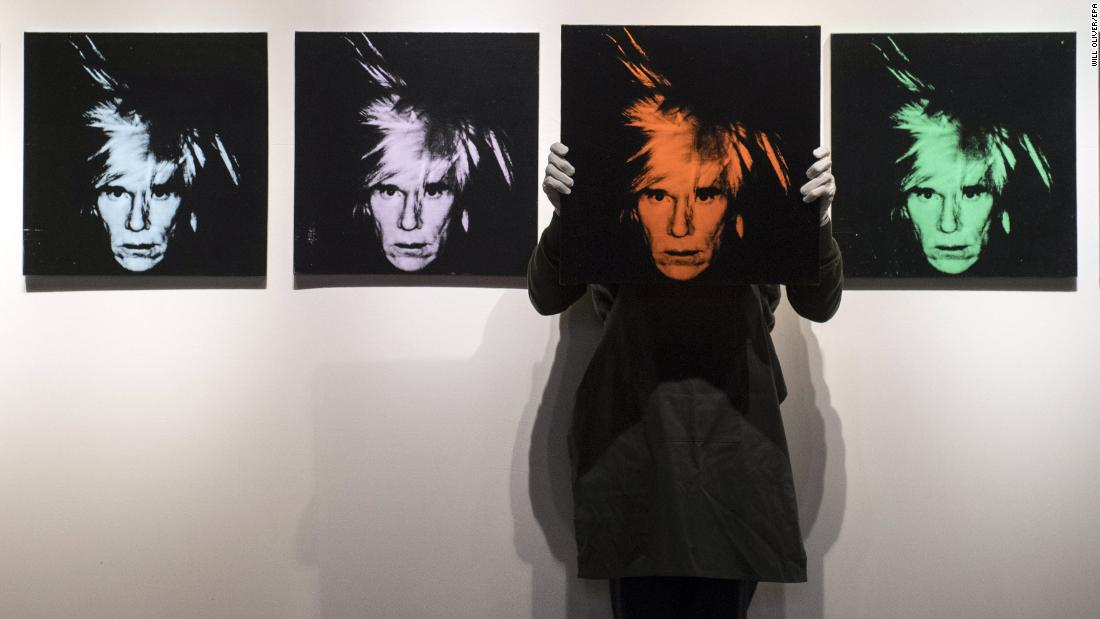An employee of the auction house Christie's holds up a self-portrait of artist Andy Warhol on Thursday, March 1. Christie's was previewing an upcoming art auction in London.