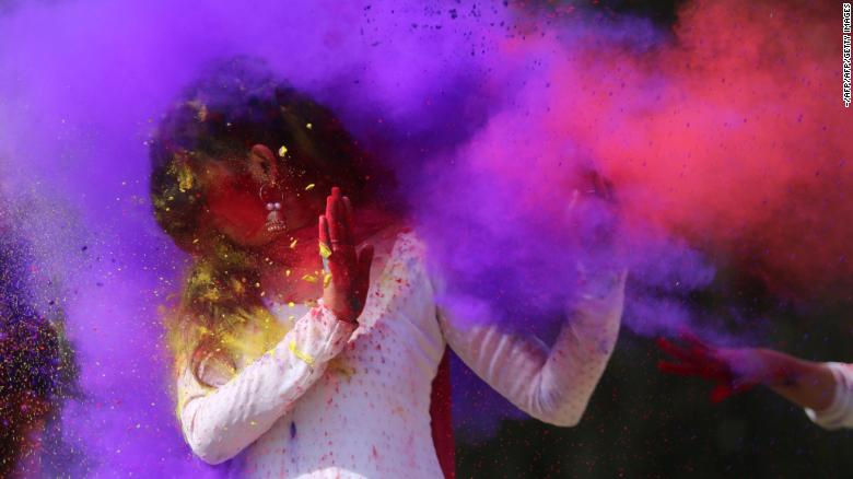 Indian college girls throw colored powder to one another during Holi festival celebrations in Bhopal on February 28, 2018.