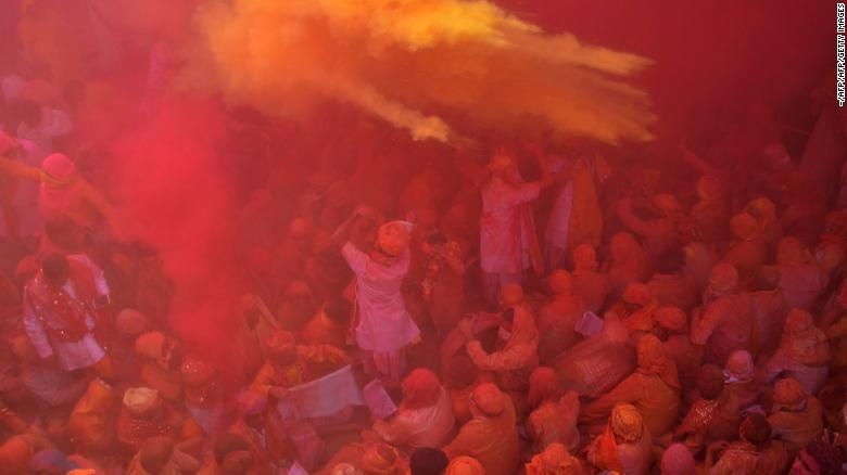 Indian Hindu devotees throw colored powder during celebration of Holi Festival at Sriji temple in Barsana in the northern Indian state of Uttar Pradesh on February 23, 2018.