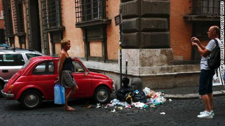 A man takes a picture of a woman standing next to an old Fiat 500 car parked in front of a pile of rubbish in a street of central Rome on July 23, 2016. (AFP / FILIPPO MONTEFORTE)