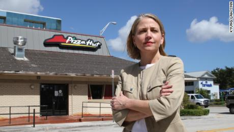 Mary Barzee Flores, now a candidate for Congress, stands outside the Pizza Hut where she was attacked as a teen.