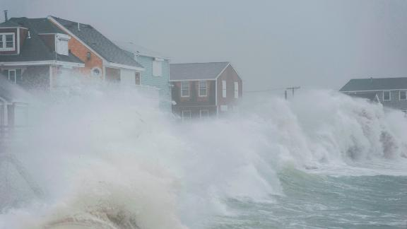 Waves crash against homes along the coast in Scituate, Massachusetts, on Friday, March 2, 2018.