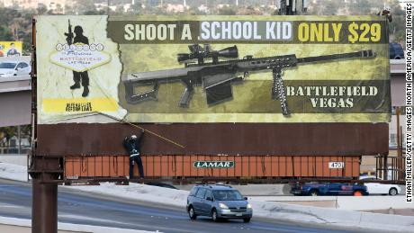 "LAS VEGAS, NV - MARCH 01:  Workers remove a billboard poster for the Battlefield Vegas shooting range after it was vandalized on March 1, 2018 in Las Vegas, Nevada. The activist art collective Indecline took responsibility for putting the words ""SCHOOL KID"" over the words "".50 CALIBER"" on the sign as well as ""Defend Lives Reform Laws"". Indecline released a statement saying that the protest piece is a response to American's obsession with gun culture and the government's ties with the NRA and called on politicians to work on reforming gun laws.  (Photo by Ethan Miller/Getty Images)"