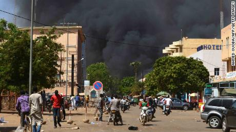 People watch as black smoke rises as the capital of Burkina Faso came under multiple attacks on March 2, 2018, targeting the French embassy, the French cultural centre and the country's military headquarters.