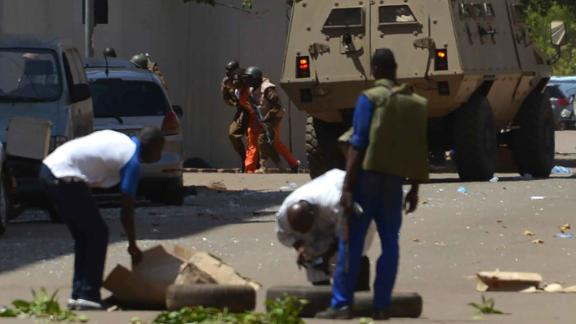 Bystanders look on as security personnel move beside an armoured personnel carrier in Ouagadougou on Friday.