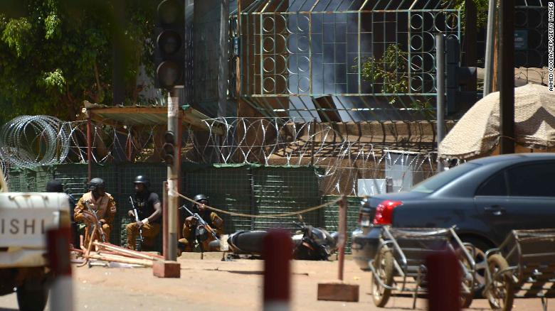 Security personnel take cover as smoke billows Friday from the French Institute in Ouagadougou.