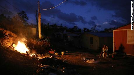 A resident sits outside her home, which lacks electricity, as a trash fire burns in San Isidro, last December.