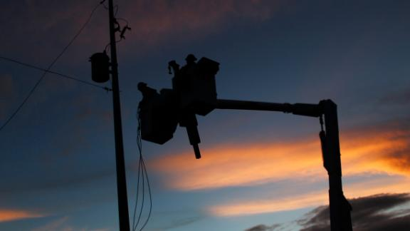 Puerto Rico Electric and Power Authority linemen works on a new utility pole placed in a residential area during sunset in Gurabo, last November.