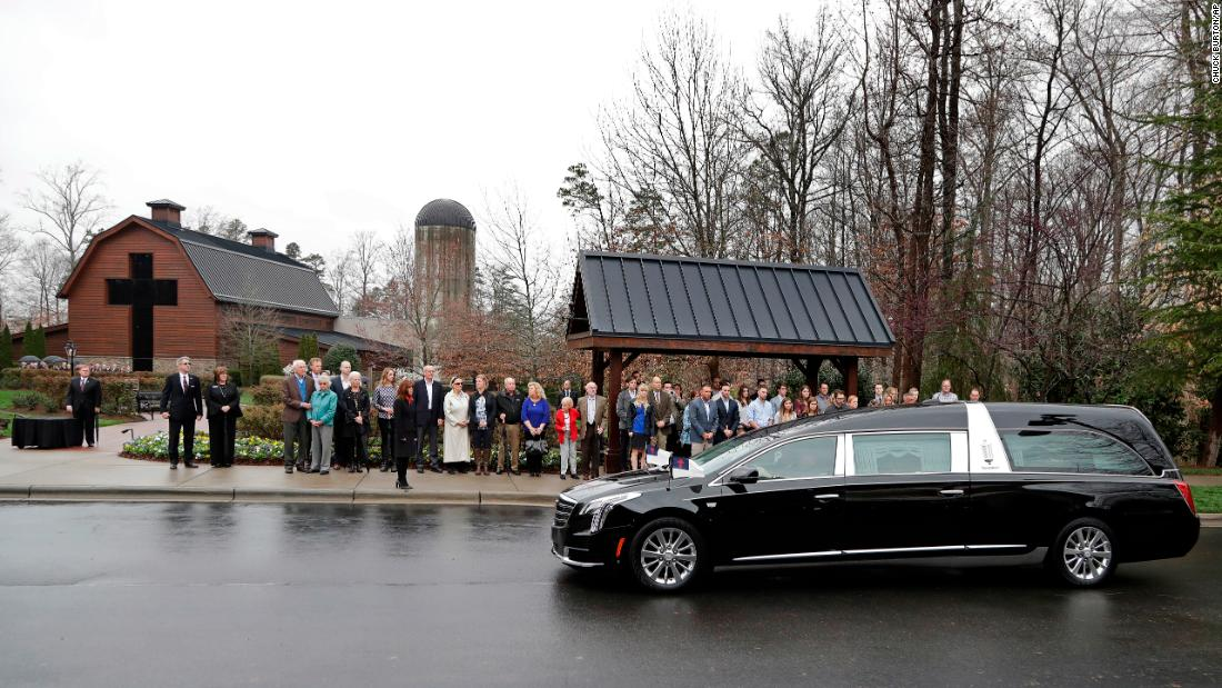 Family members look on as a hearse carrying Graham's body returns from Washington on Thursday, March 1. Graham was lying in honor at the US Capitol.