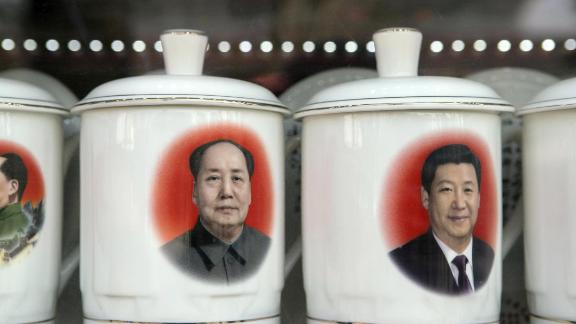 Porcelain cups featuring portraits of Chinese President Xi Jinping, right, and former Chinese leader Mao Zedong stand on display at a store window in Beijing, China, on Monday, Feb. 26, 2018. Xi is China's most powerful leader since Mao.