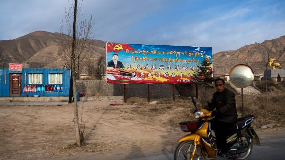 A motorcyclist rides past a propaganda poster showing China's President Xi Jinping next to a freeway outside of Tongren, Qinghai province on March 2, 2018.