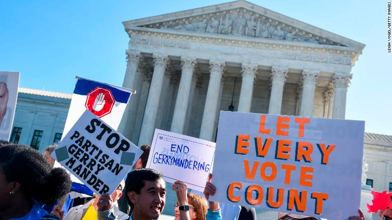 "People hold signs during a rally to call for ""An End to Partisan Gerrymandering"" at the Supreme Court of the United States on October 3, 2017 in Washington, DC."