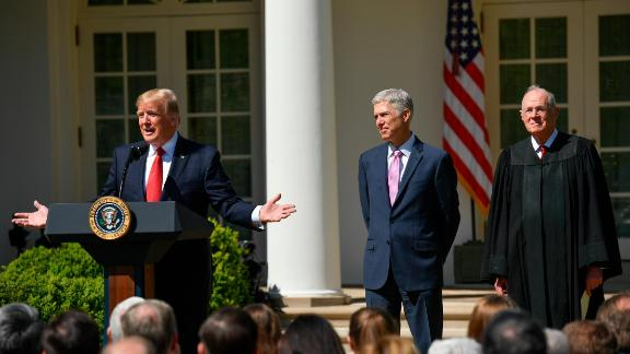 Supreme Court Justice Neil Gorsuch, center, along side Justice Anthony Kennedy, right, listen as President Donald Trump speaks on April 10, 2017 in Washington, D.C.
