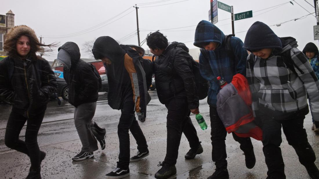 Schoolchildren face off against the wind and rain as they walk home in Brooklyn, New York, on March 2.