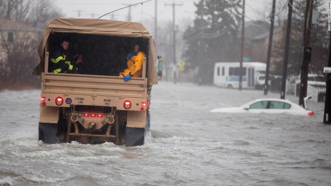 A National Guard vehicle carries emergency workers to residents trapped by floodwaters in Quincy on March 2.
