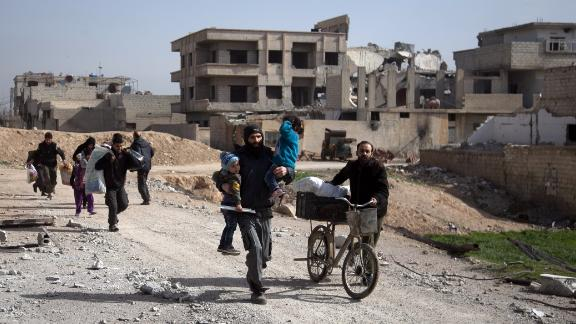 Syrians flee their homes with their belongings in the town of Beit Sawa in Syria's besieged eastern Ghouta region on March 4, 2018, following reported air strikes.