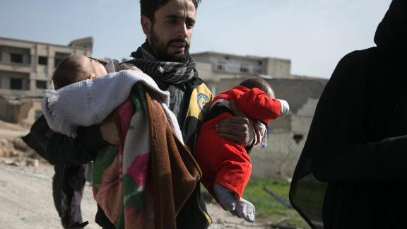 A Syrian civil defence volunteer carries children as he helps them try to flee their homes in the town of Hamouria in Syria