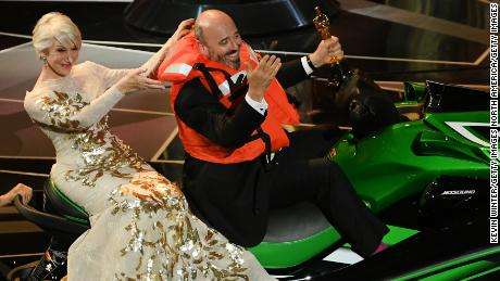 Helen Mirren with Oscar-winning costume designer Mark Bridges sitting on a Jet Ski, which he received as a prize for shortest acceptance speech.