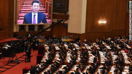 A live image of Chinese President Xi Jinping is seen on a screen above delegates during the opening session of the National People's Congress in the Great Hall of the People in Beijing on March 5, 2018.