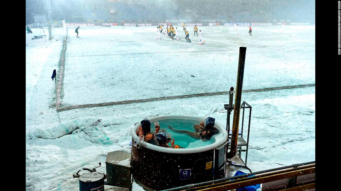 Soccer fans in Hobro, Denmark, watch a match from a hot tub on Wednesday, February 28. They won a contest to get their unique view.