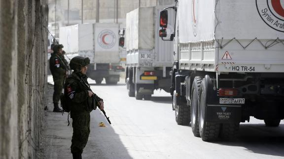 Russian soldiers stand guard as Syrian Arab Reb Crescent trucks carrying aid drive past on March 5.
