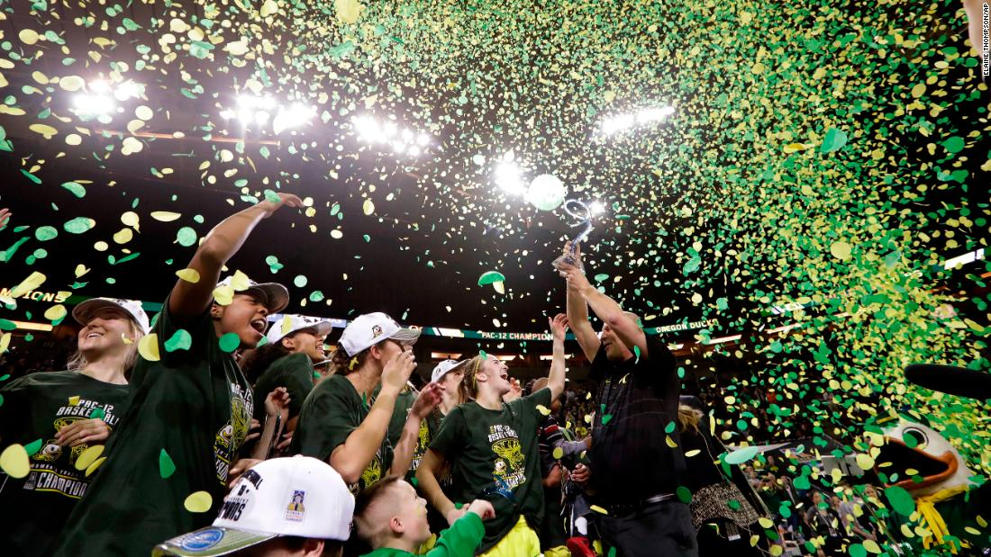 Kelly Graves, head coach of the women's basketball team from Oregon, lifts the trophy after the Ducks won the Pac-12 Conference tournament on Sunday, March 4.