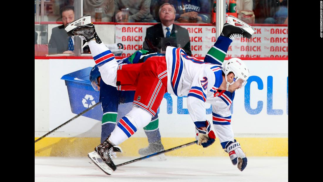 Chris Kreider, foreground, is checked by Alexander Edler during an NHL game in Vancouver, British Columbia, on Wednesday, February 28.
